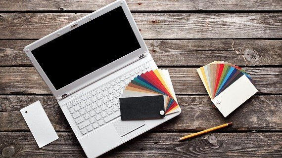 White laptop with designer color swatches on old wooden table.